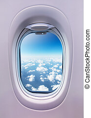 Airplane interior with window view of clouds.