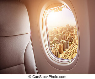 Airplane interior with window view of Dubai city