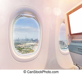 Airplane interior with window view of Dubai city, UAE.