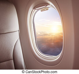 Airplane interior with window view of sunset above clouds.