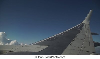 Airplane is flying in the blue sky through the white clouds. View of the airplane wing from the window.