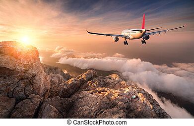 Airplane is flying over clouds at sunset