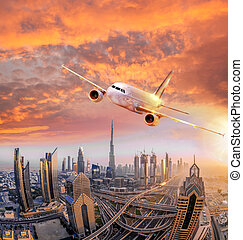 Airplane is flying over Dubai against colorful sunset in...