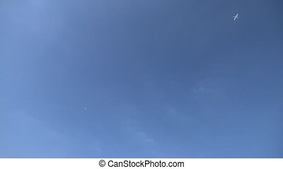 Two passenger commercial airplanes crossing flying, isolated in the blue sky. View from below ground level.