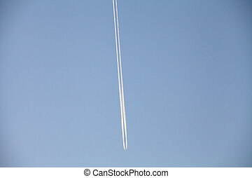Picture of an airplane in the sky with jet trail