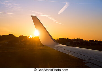Airplane jet wing at sunset with golden sunlight