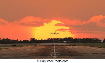 airplane landing across the sun