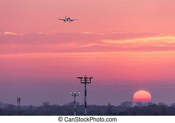 airplane landing at an airport in an evening sundown
