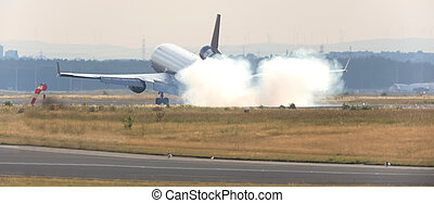 airplane landing at an runway with tire smoke cloud