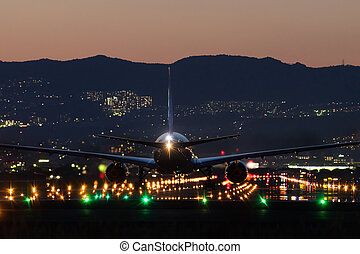 Airplane landing at dusk