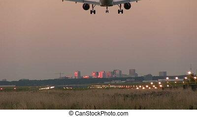 Airplane landing at dusk