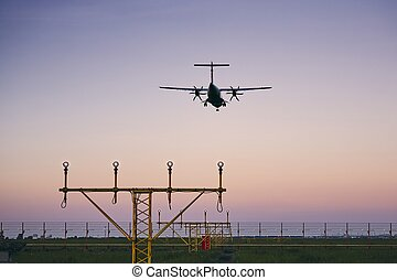 Airplane landing at dusk. Turboprop aircraft approaching to...