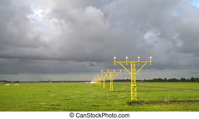 Airplane landing at illuminated runway - Airplane landing on...