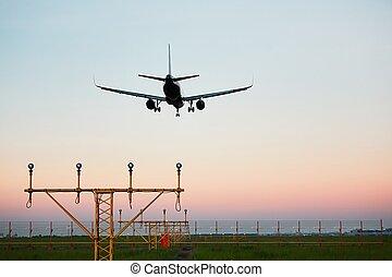 Airplane landing at the sunset