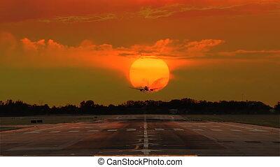 airplane landing crossing sun