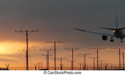 Airplane landing in airport at sunset, Los Angeles, California USA. Passenger flight or cargo plane silhouette, dramatic cloudscape. Aircraft arrival to airfield. International transport flying