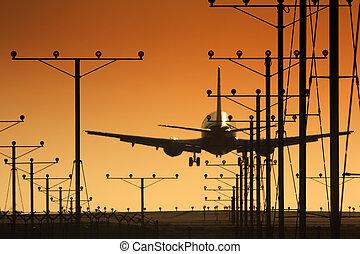 Airplane landing in airport at sunset - Plane landing in...