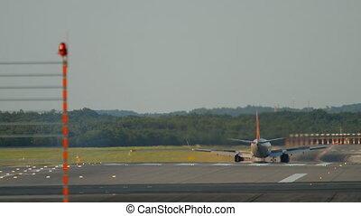 Airplane braking after landing at 05R runway Dusseldorf airport, evening sunset rays