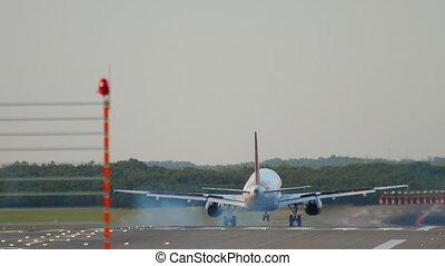 Airplane landing at 05R runway Dusseldorf airport, evening sunset rays