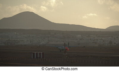 Airplane landing in scenic town with hills landscape -...