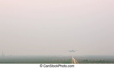 Airplane landing on runway in fog