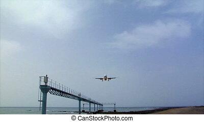 airplane landing over seaside audio