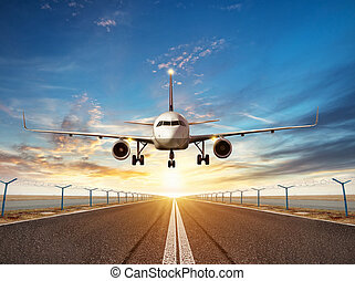 Airplane landing to airport runway in sunset light -...