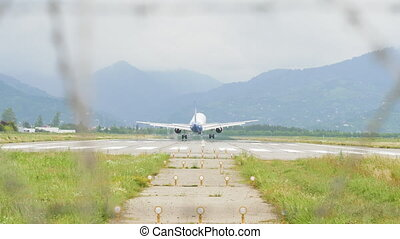 Airplane landing to the airport in mountains - Georgia