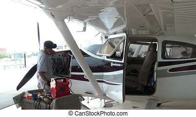 Airplane mechanic works hard on a propeller planes engine with tools on sunny summer day.