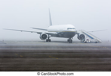 Airplane mist haze - Airplane on the landing strip covered...