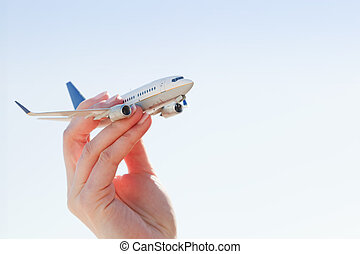 Airplane model in hand on sunny sky. Concepts of travel, transportation