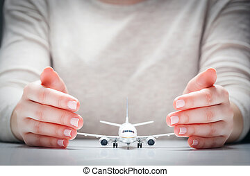 Airplane model surrounded by hands in gesture of protection. Aircraft industry safety, insurance