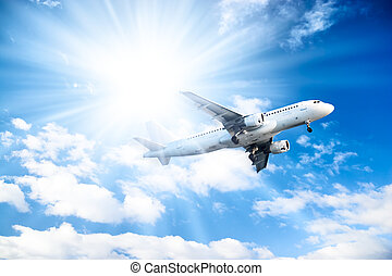 Airplane on blue sky and bright sun background.