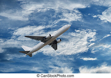 airplane on sky with fluffy and spindrift clouds