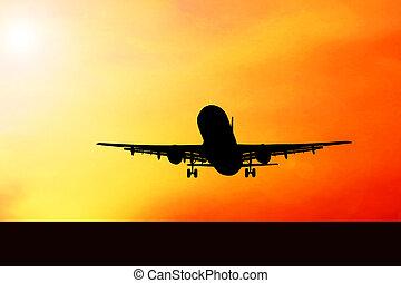 Airplane on sunset sky