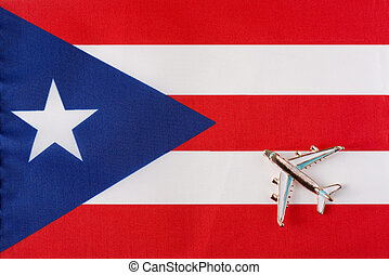 Airplane over the flag of Puerto Rico travel concept.