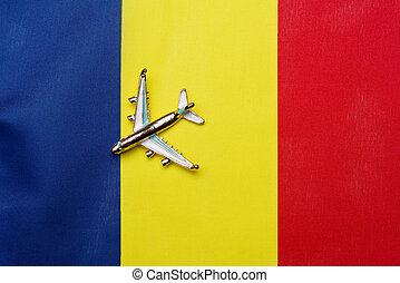 Airplane over the flag of Romania travel and tourism concept.