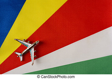 Airplane over the flag of Seychelles travel concept.