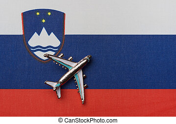 Airplane over the flag of Slovenia, the concept of travel.