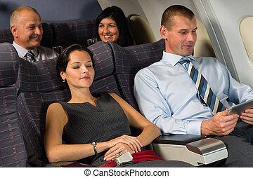Airplane passengers relax during flight cabin sleep businesspeople