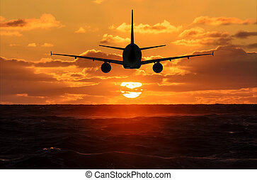 Airplane in the sky is flying into the sunset over the sea...