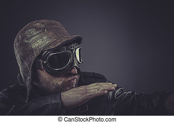 airplane, pilot dressed in vintage style leather cap and goggles