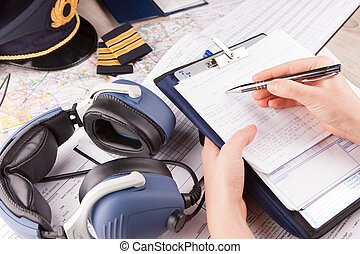 Airplane pilot filling in flight plan - Close up of an...