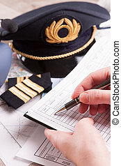 Airplane pilot filling in flight plan - Close up of an ...