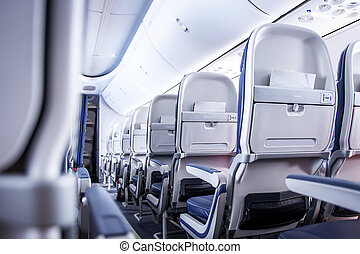 Airplane seats in cabin. Commercial aircraft cabin with rows of seats down the aisle. Economy class.
