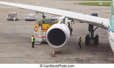 Airplane standing at airstrip is filled with fuel by service...