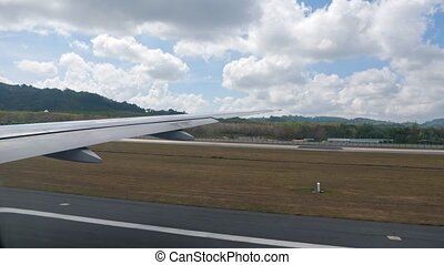 airplane takeoff from the strip with wing on foreground. hilly beautiful green landscape against blue cloudy sky view from window.