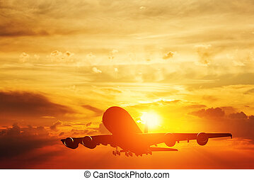 Airplane taking off at sunset. Silhouette of a flying...