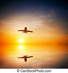 Airplane taking off at sunset. Silhouette of a big passenger or cargo aircraft, airline flying. Abstract water reflection. Transportation