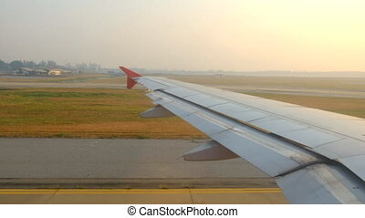 Airplane taxiing on runway at airport in morning, view through from window